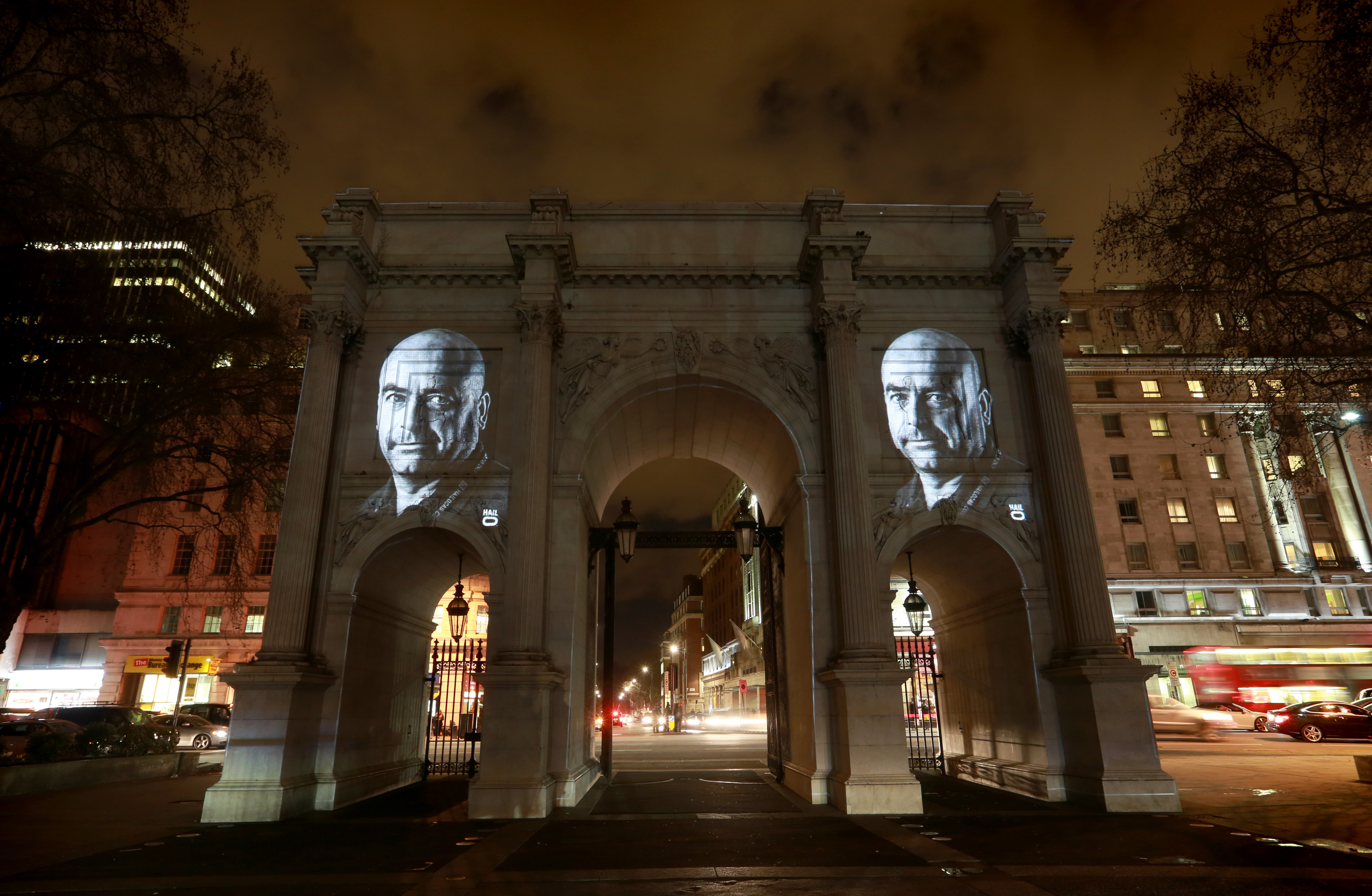 A portrait of Micky Eales, a London cabbie, is projected onto Marble Arch in London as part of the Hailo Face to Faceless Campaign