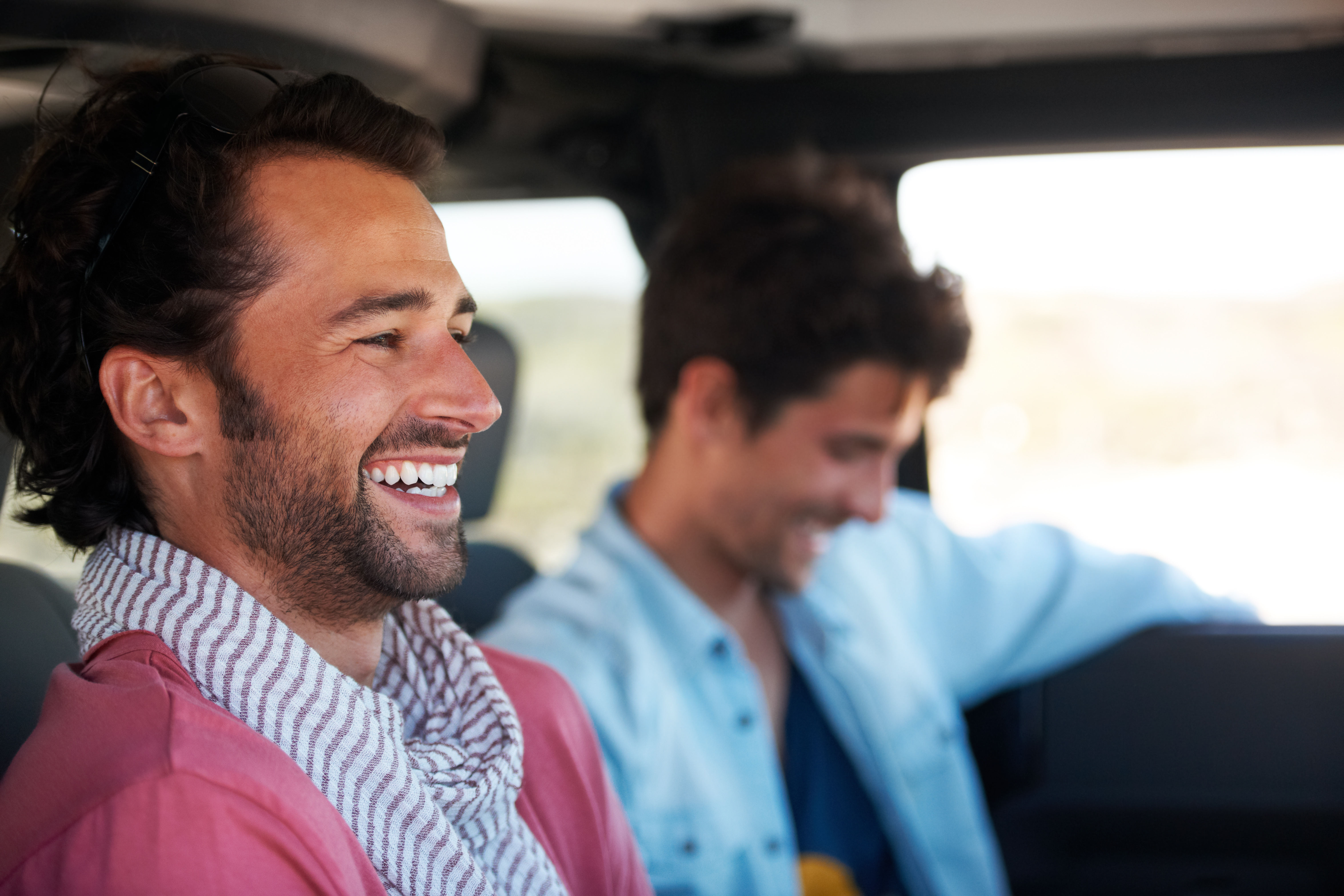 Two friends happy and laughing together while on a drive